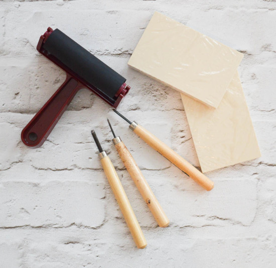 A brayer (like a rubber roller), stamp blocks and small carving tools