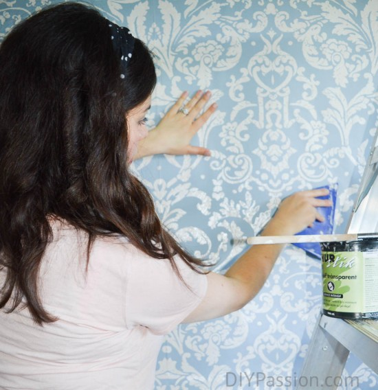 Work quickly on the pasted wall to smooth down the paper