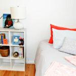small white bookshelf next to a bed