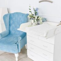 blue chair and changing table for infants. interior of a spacious children's room. changing table topper