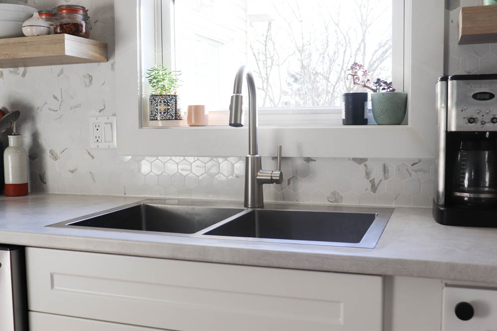 stainless steel kitchen sink in front of a window with tile backsplash