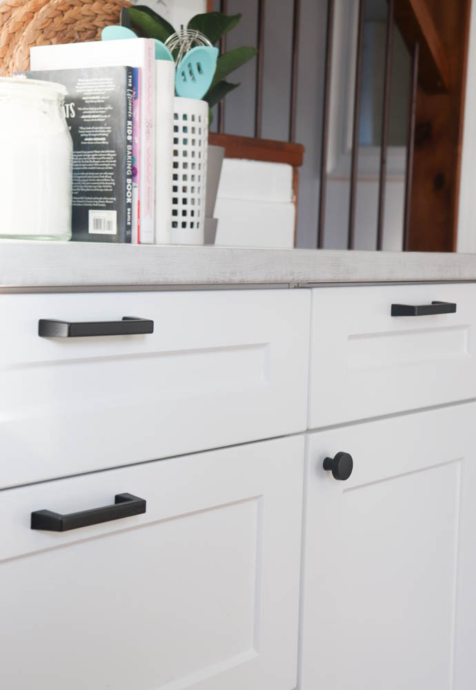 close up of white shaker cabinets and black hardware
