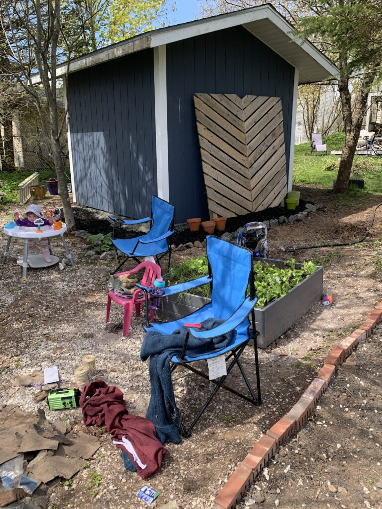 blue painted shed with privacy wall and camping chairs in foreground